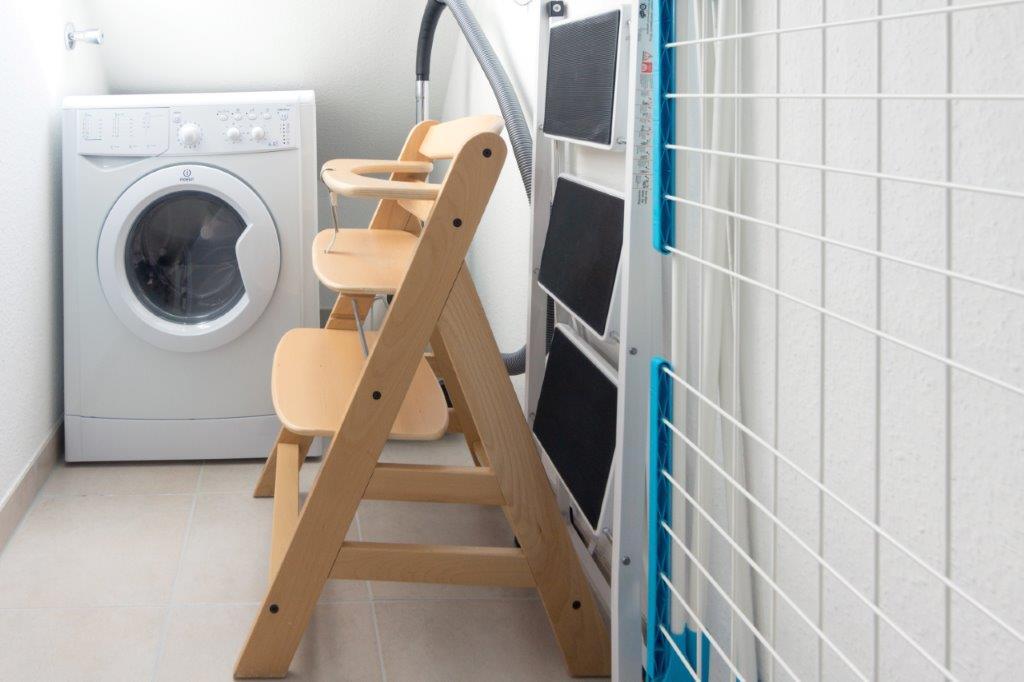 Wirtschaftsraum mit Waschmaschine, Kinderhochstuhl und Kinderreisebett