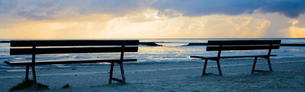 2 Sitzbänke am Strand von Norddeich bei Sonnenuntergang