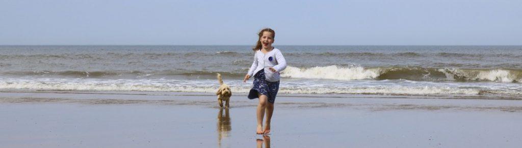 Mädchen und Hund rennen am Strand vor den Wellen davon