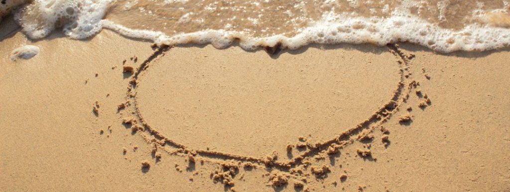 Herz in den Sandstrand gezeichnet
